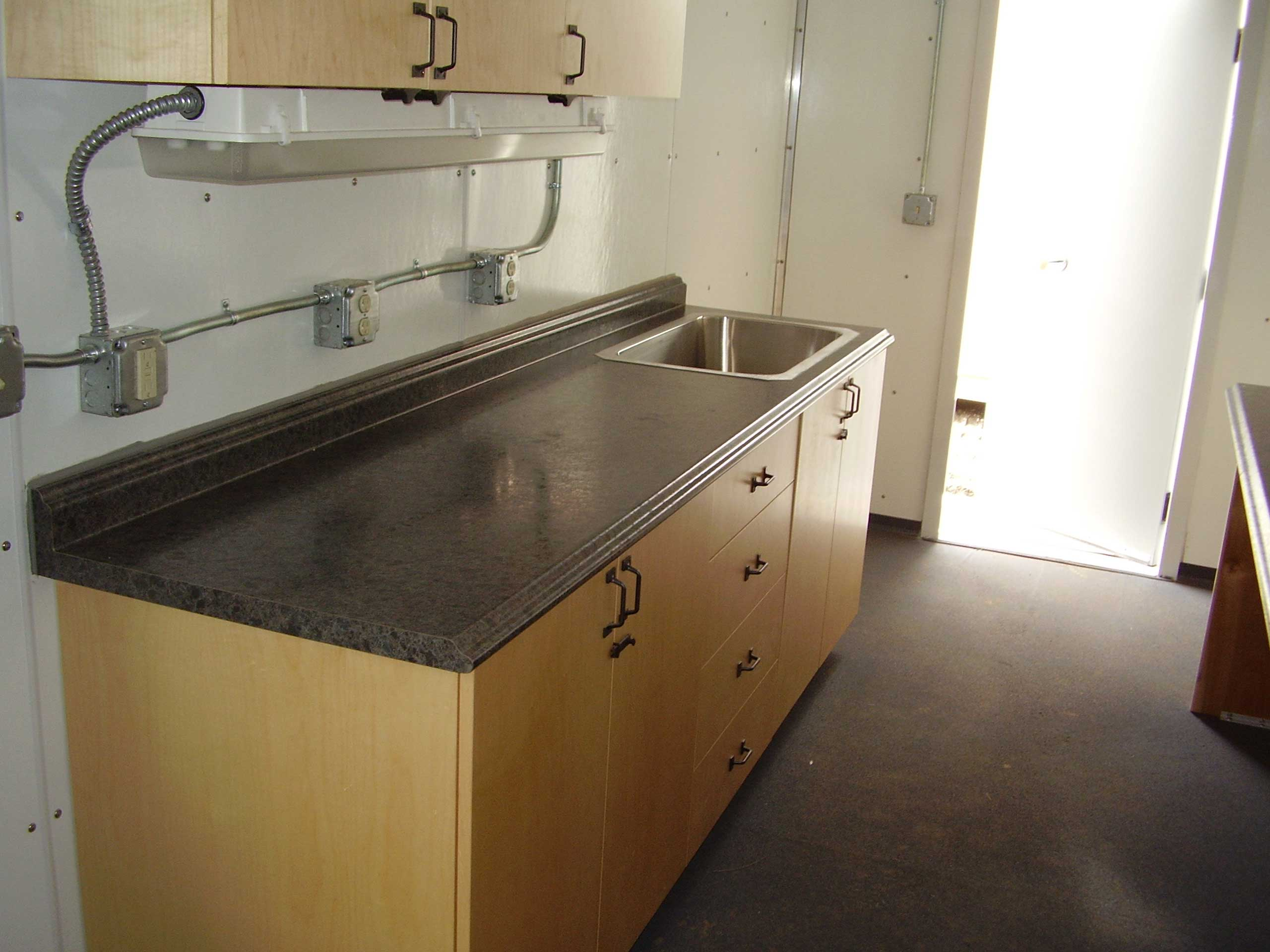 Sperry Drilling needed custom containers created to use as mud rooms in field.  Each Mud Room needed secure human-sized doors with porches for safe transit into the container.  Each container needed windows for natural lighting, easy-to-clean wall paneling, flooring, cabinets, counter tops, lighting, electrical outlets, and a sink basin to meet their custom needs.