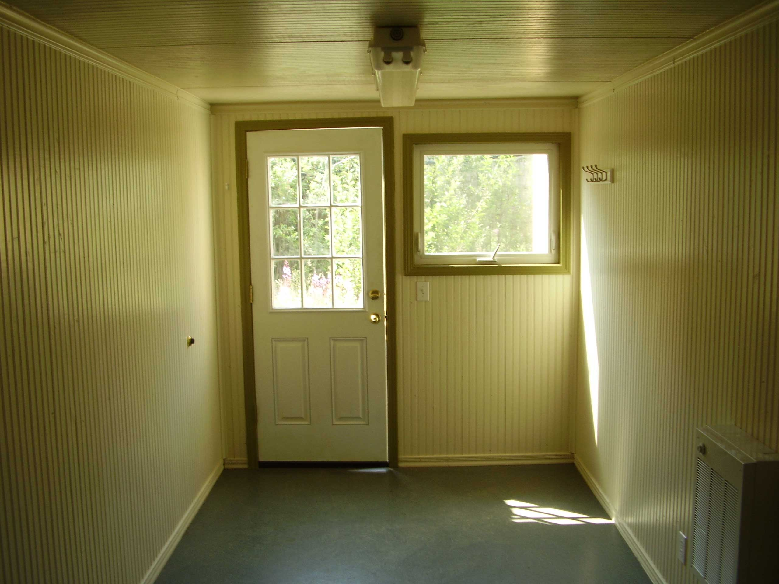 Office entry door, window-panes for natural lighting, painted interior wood-panelling with commercial carpet, wall heating system, and fluorescent lighting fixtures for a comfortable working environment for employees as either a temporary on-site office space, or off-site field office.